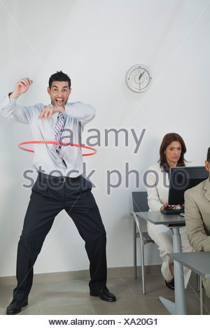 Young businessman playing with hula hoop in office while colleagues work - Stock Photo