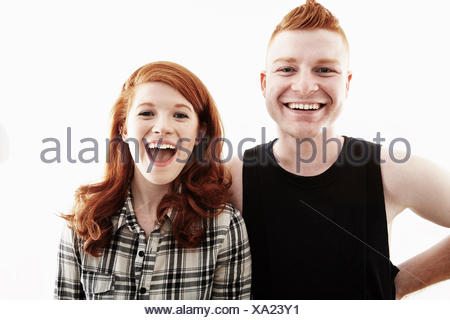 Studio portrait of red haired young couple laughing - Stock Photo