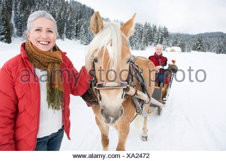 Italy, South Tyrol, Seiseralm, Senior woman standing by horse, man sitting in sleigh, smiling, portrait - Stock Photo