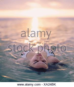 Young woman floating in the sea, Sanibel Island, Florida, USA - Stock Photo