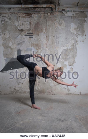 Mid adult woman practicing sugarcane pose in yoga studio, Munich, Bavaria, Germany - Stock Photo