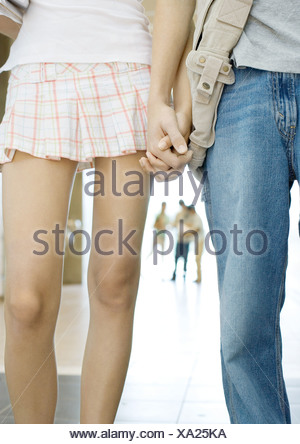 Teenage couple holding hands, close-up of mid-section - Stock Photo