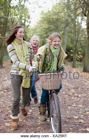 Mother helping daughter ride bicycle - Stock Photo