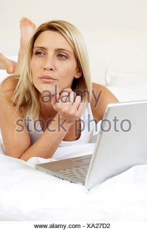 Young woman in bed working on laptop - Stock Photo