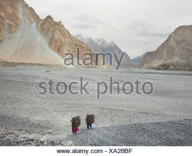 Women returning home after getting wood for cooking and heating, a two hour walk. - Stock Photo