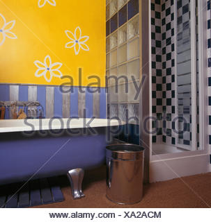 Stylised flowers drawn on wall above roll top bath in bright yellow nineties bathroom with glass shower cabinet - Stock Photo