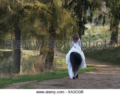 Rear view of a mature woman riding a horse in a white dress - Stock Photo