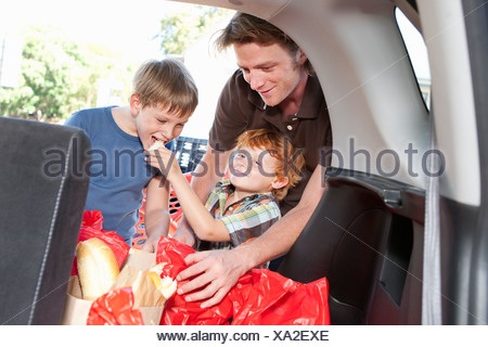 Boys eating groceries in trunk of car - Stock Photo