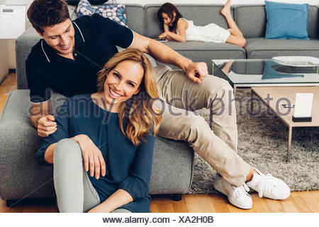 Smiling couple in living room with daughter using digital tablet in background - Stock Photo