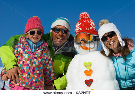 group photo of a family of three in winter clothing with a snowman during holidays in the mountains, France - Stock Photo