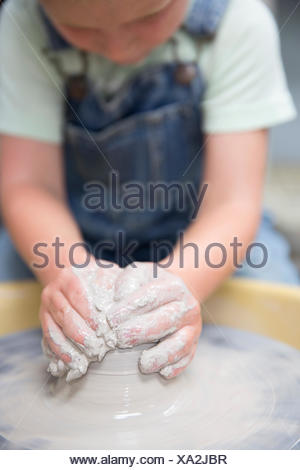 Boy shaping clay on potter's wheel - Stock Photo