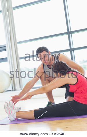 Trainer assisting woman with pilate exercises in fitness studio - Stock Photo