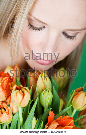 A young woman looking at a bunch of orange tulips, looking down - Stock Photo