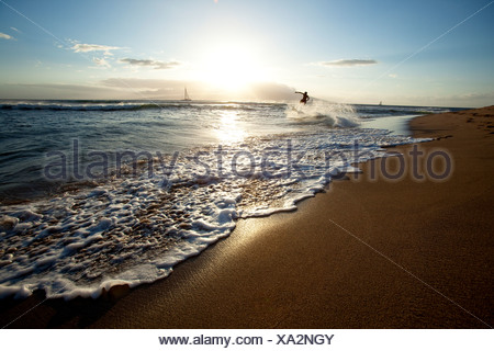 One man skimboarding at sunset with sailboats in the background. - Stock Photo