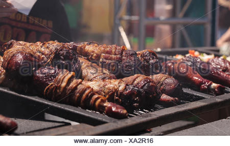 Bacon wrapped around turkey legs on a barbecue to cook at a fair ground. - Stock Photo