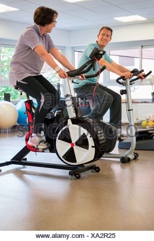 Man and woman in a spinning class at the gym - Stock Photo