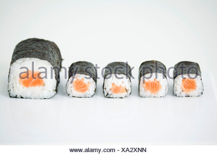 Five pieces of maki sushi arranged in row, end piece larger than others - Stock Photo