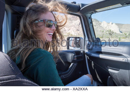 A girl sits in the passenger seat of a jeep on a road trip through Joshua Tree National Park. - Stock Photo