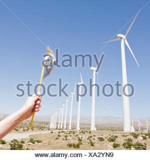 USA,California,Palm Springs,Coachella Valley,San Gorgonio Pass,Woman's hand holding pinwheel against blue sky and wind turbines - Stock Photo