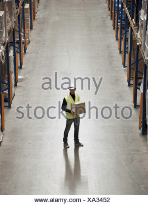 Worker carrying box in warehouse - Stock Photo