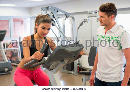 Instructor teaching a woman in spinning class at gym - Stock Photo