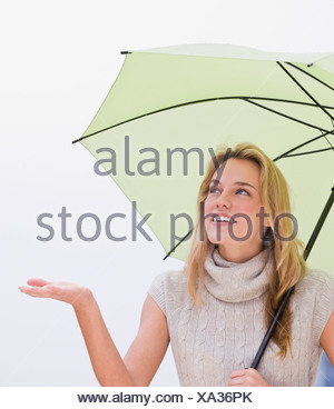 Woman holding hand out from under umbrella - Stock Photo