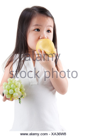 Little Asian girl eating pear and grapes, on white background - Stock Photo