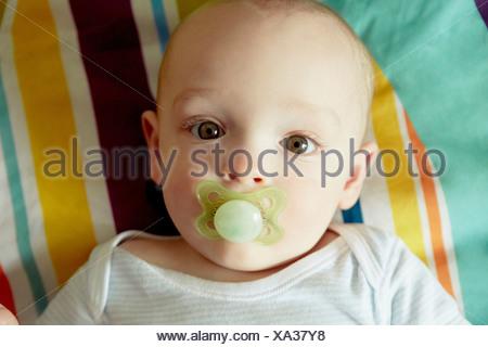 Portrait of baby boy sucking pacifier - Stock Photo