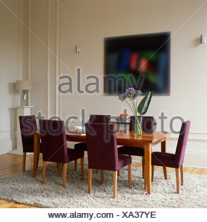 Purple Upholstered Chairs At Plain Wood Table In Modern Dining Room With White Shag Pile Rug