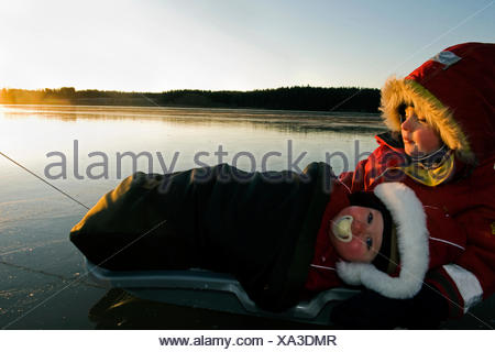 Two children in a little sledge on the ice, Sweden. - Stock Photo