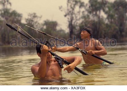 Xingu, Amazon rainforest, Brazil. Yaulapiti indigenous People. Tuatuari river. Acculturated young indians fishing with harpoon. - Stock Photo