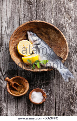 Fresh raw fish seabass with salt, spices and lemon on textured wooden background - Stock Photo