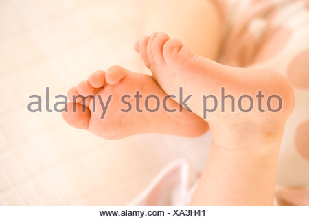 Baby girl 9-12 months, close-up of feet - Stock Photo