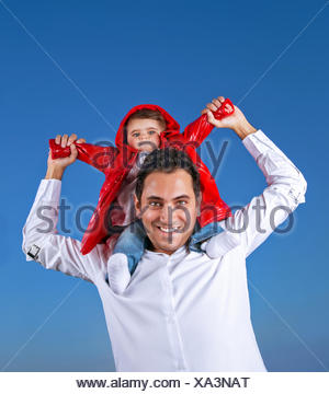 Portrait of cheerful young father with cute little son sitting on his shoulders on blue clear shy background, having fun outdoors - Stock Photo