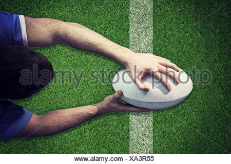 Composite image of a rugby player scoring a try - Stock Photo