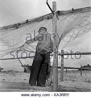Ein Fischer bei Rositten an der Ostsee sortiert seine Netze, Ostpreußen, Deutschland 1930er Jahre. A fisherman assorting his net at Rositten on the Baltic Sea in East Prussia, Germany 1930s. - Stock Photo