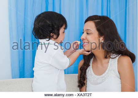 Baby boy feeding chips to his mother - Stock Photo