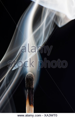 Smoking match against black background - Stock Photo