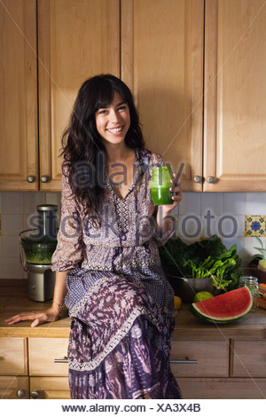Young woman in kitchen with vegetable juice - Stock Photo