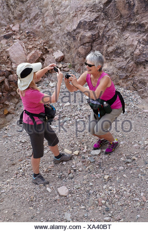 Two senior female hikers photographing each other - Stock Photo