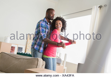 Mid adult couple dancing in new home - Stock Photo