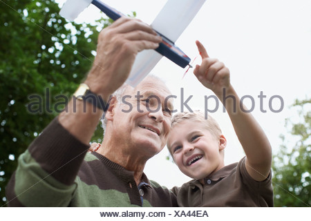 Grandfather showing grandson toy airplane - Stock Photo