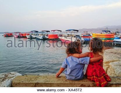 Rear View Of Siblings Relaxing On Retaining Wall - Stock Photo