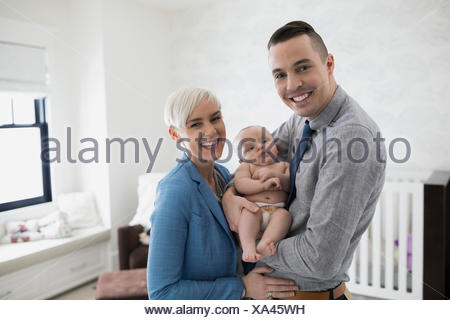 Portrait smiling parents holding baby son in nursery - Stock Photo
