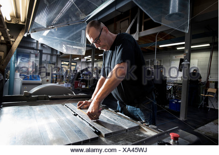 Worker servicing print machine in printing workshop - Stock Photo