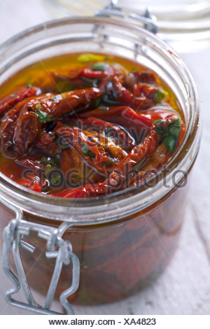 Dried tomatoes in a jar with olive oil - Stock Photo