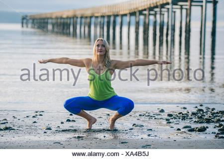 Portrait of young woman crouching in yoga pose on beach - Stock Photo