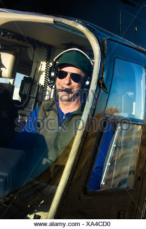 Portrait of helicopter pilot sitting in cockpit looking at viewer - Stock Photo
