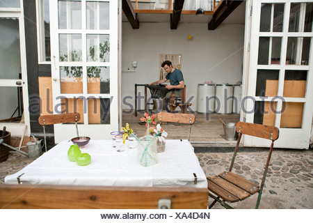 Table and chairs in artist's courtyard - Stock Photo