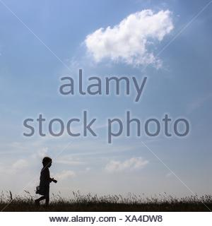 Silhouette of girl walking in rural landscape - Stock Photo